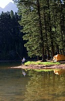 Solitary man, in mid-distance, fishing in lake on camping trip, side view