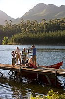Multi-generational family standing on lake jetty beside motorboat, man holding fish, side view