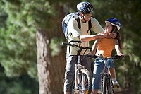 Father and daughter 7-9 mountain biking on woodland trail, man adjusting strap of girl's cycling helmet