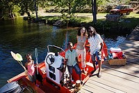 Family standing in motorboat moored at lake jetty, children 7-10 holding fishing equipment, smiling, portrait