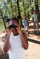 Family hiking on woodland trail, focus on girl 7-9 looking through binoculars in foreground