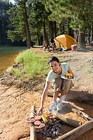 Family having lunch on camping trip by lake, focus on woman cooking food in foreground, smiling, portrait