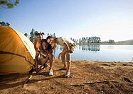 Family crouching beside tent on lakeside camping trip, smiling, portrait
