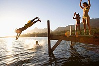 Father and son 8-10, in swimwear, diving off jetty into lake at sunset, mother and daughter 7-9 cheering lens flare
