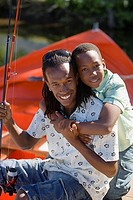Boy 8-10 embracing father on camping trip, man holding fishing rod, smiling, portrait