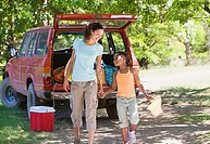Mother and son 8-10 unloading parked SUV on camping trip, holding hands, smiling