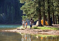 Family, in mid-distance, fishing beside lake on camping trip, woman holding catch, man with fishing rod