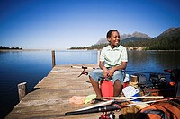 Boy 8-10 sitting on coolbox beside moored motorboat on lake jetty, looking at scenery, smiling