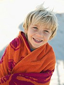 Blonde boy 6-8 standing on beach, wrapped in orange towel, smiling, close-up, portrait tilt