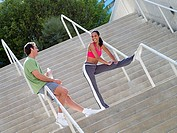Couple, in sportswear, warming down from jog, man leaning against railing on steps, woman stretching leg tilt