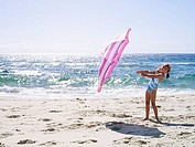 Girl 7-9, in swimsuit, playing with pink parasol on sandy beach near water¥+++§¥s edge, smiling, side view, portrait