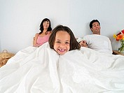 Family resting in double bed at home, focus on girl 5-7 wrapped in duvet, laughing, portrait