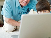 Senior man and grandson 5-7 using laptop on living room floor, smiling, front view, close-up