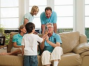 Multi-generational family relaxing on sofa at home, boy 5-7 showing grandfather mobile phone, smiling