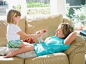 Senior woman lying on sofa at home, granddaughter 6-8 sitting in grandmother¥+++§¥s lap, feeding her strawberries, side view