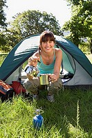 Young woman crouching beside dome tent in woodland clearing, taking boiled kettle from camping stove, smiling, portrait