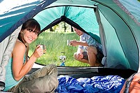 Young woman sitting inside dome tent, drinking hot drink, man crouching beside camping stove outside, smiling, portrait