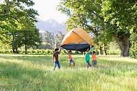 Four young adults carrying orange dome tent above head on camping trip in woodland clearing, side view