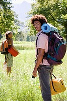 Young couple, with rucksacks, standing in woodland clearing, departing on hiking trip, man carrying sleeping bag, smiling, portrait