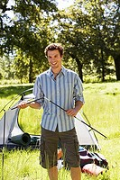 Young man assembling dome tent on camping trip in woodland clearing, smiling, portrait