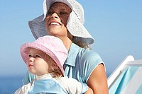 Mother and daughter 2-3 sitting on beach in deckchair, wearing sun hats, smiling, close-up