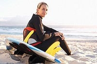 Woman sitting on sandy beach in wetsuit, holding surfboard, smiling, side view, portrait