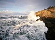 USA, Oregon, waves crashing against sandstone bluff