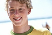 Blonde boy 12-14 standing on beach, smiling, portrait (thumbnail)
