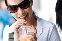 Thailand, Bangkok, Thai woman smiling with drink