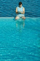Man sitting in infinity pool, reading