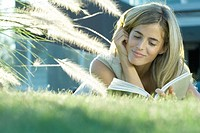 Young woman lying in grass, reading book