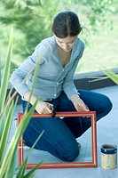 Young woman painting picture frame outdoors