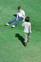 Boy walking across grass toward second boy