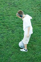 Boy standing with ball, wearing headphones