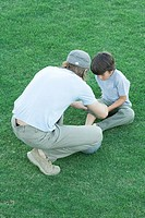 Boy sitting on grass with pants leg rolled up, man leaning over him