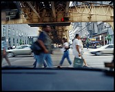 Pedestrians walk underneath L tracks in downtown Chicago