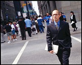 Man in business suit holding newspaper crosses street with people in background