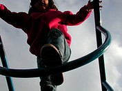 Low angle shot of young girl climbing on jungle gym