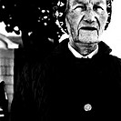Cropped image of elderly woman in hat and coat standing outside