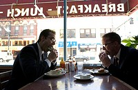 Two men in suits and glasses eat sandwiches in diner