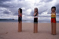 Three decorated bollards on beach