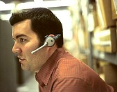 Profile of businessman in warehouse, talking on headset