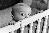 Baby climbing up side of crib, looking at camera'