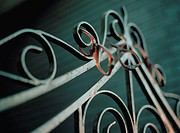 Three pairs of broken glasses frames hanging from scrollwork on wrought iron gate