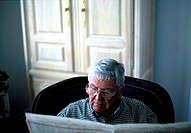 Older man reads newspaper indoors