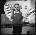 Little girl bending photographer's reflector to look like angel wings