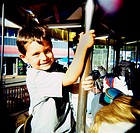 Young boy hangs on to pole on carousel