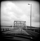 Black and white view out of moving car on bridge