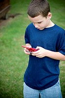 Young boy playing handheld video game in park