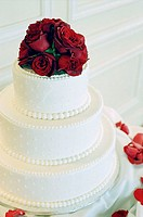 Wedding cake with red roses on top